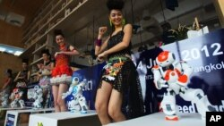FILE - Humanoid robots called Nao, developed by a French company, Aldebaran Robotics, dance along with models to mark the opening of a press conference of the Manufacturing Expo in Bangkok,