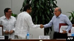 FARC guerrilla commander Ivan Marquez, center, and the head of the Colombian delegation for peace talks, Humberto de la Calle, shake hands after signing a new peace agreement next to Cuban Foreign Affairs Minister Bruno Rodriguez Parrilla in Havana, Nov. 12, 2016.