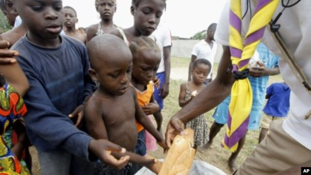 A man distributes bread to children at St. Ambrose church in Angree, Abidjan, a temporary refuge for people fleeing from clashes between forces loyal to incumbent president Gbagbo and his rival Ouattara (File Photo - March 1, 2011)