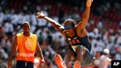 FILE - United States' Lex Gillette, right, jumps as his escort, left, looks on during the men's Triple Jump F11 at the Beijing 2008 Paralympic Games in Beijing, China, in this Sept. 12, 2008, file photo.