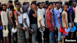 Men who fled fighting in Ethiopia's Tigray region queue for food rations at Um-Rakoba camp, on the Sudan-Ethiopia border, in Al-Qadarif state, Sudan, Nov. 19, 2020.