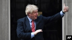 "Britain's Prime Minister Boris Johnson joins in the applause on the doorstep of 10 Downing Street in London during the weekly ""Clap for our Carers"" Thursday, May 7, 2020. The COVID-19 coronavirus pandemic has prompted a public display of appreciation for…"
