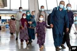 Families evacuated from Kabul, Afghanistan, walk through the terminal before boarding a bus after they arrived at Washington Dulles International Airport, in Chantilly, Va., Aug. 23, 2021.