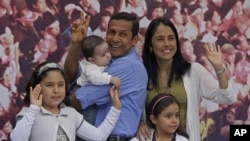 Peru's presidential candidate Ollanta Humala, of the political party Gana Peru, second left, and his family pose for photos during a traditional Peruvian breakfast on their patio in Lima, Peru, June 5, 2011