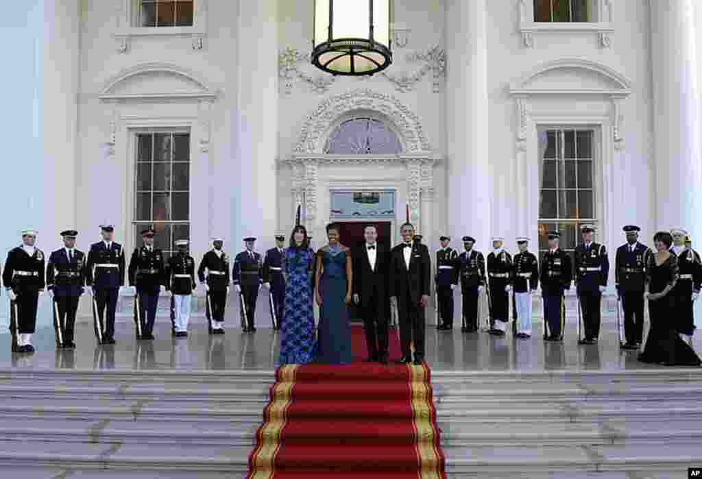 Mr. and Mrs. Obama pose for photographers with Mr. and Mrs. Cameron as they arrive in the North Portico of the White House prior to a State Dinner. (AP)