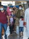 Porodice evakuisane iz Kabula, prolaze kroz terminal kako bi se ukrcale na autobus, nakon što su stigle u na aerodrom u Vašingtonu, 28. avgusta 2021.