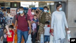 Families evacuated from Kabul, Afghanistan, walk through the terminal to board a bus after they arrived at Washington Dulles International Airport, in Chantilly, Va., Aug. 28, 2021.