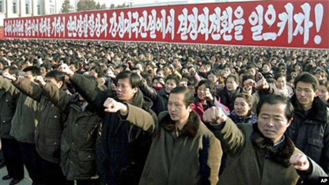 People pump their fists as about 100,000 North Koreans gather for an annual New Year rally to display loyalty to leader Kim Jong Il in Pyongyang, 03 Jan 2011