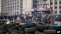 People are seen gathered in front of a barricade at the regional administration building in Donetsk, Ukraine, April 9, 2014.