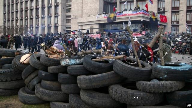 Dân chúng tụ tập trước một hàng rào chướng ngại dựng trước tòa nhà chính quyền ở Donetsk Ukraine, 9/4/14