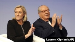 Jean-Marie Le Pen, à droite, applaudit aux côtés de sa fille Marine Le Pen, lors d'une réunion du Front National (AP Photo/Laurent Cipriani, File)