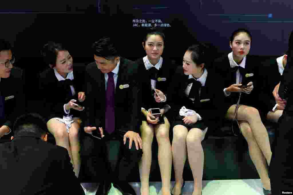 """2018年4月25日,在第十五届北京国际汽车展览会上,一些工作人员在江淮汽车展台休息。 这张照片以女性为主,但总的来说,中国就业市场存在重男轻女现象。4月23日,人权观察组织在香港公布的报告显示,中国政府企业和民营企业招工过程中惯用一些歧视性招聘广告。2018年,中国国家机关公务员广告中,几乎每五则中就有一则限招男性,或者""""男性优先""""。阿里巴巴公司在招聘启事中,则许诺应征者将与""""美女""""为同事,以美女员工招徕异性人才。"""