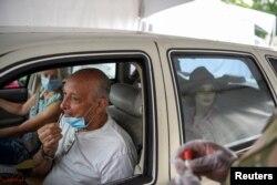 Seseorang menggunakan usap hidung untuk memberikan sampel yang akan diuji untuk COVID-19 di tempat pengujian drive-thru ketika kasus melonjak di seluruh negara bagian, di New Orleans, Louisiana, AS, 6 Agustus 2021. (Foto: Reuters)
