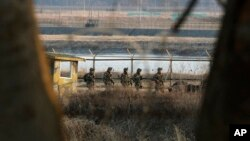 South Korean army soldiers patrol along a barbed-wire fence near the border village of Panmunjom in Paju, South Korea, Mar. 27, 2013.