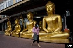 Seorang perempuan mengenakan masker, saat berjalan melewati patung Buddha emas di Bangkok, 5 Januari 2021, setelah pemerintah Thailand memberlakukan pembatasan wilayah akibat pandemi Covid-19. (Foto: Jack TAYLOR / AFP)