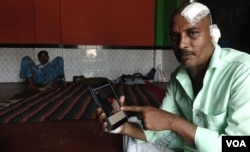 Manzoor Alam, a Muslim laborer, shows BJP MP Arjun Singh's Facebook post. Alam was beaten by a Hindu mob in Telinipara. Singh posted a photo of bloodied Alam on Facebook and said he was a Hindu who had been beaten by Muslims. (Shaikh Azizur Rahman/VOA)