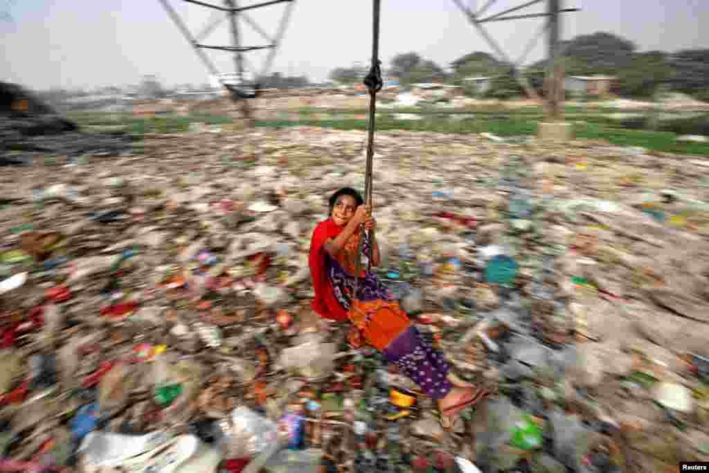 Seorang anak perempuan bermain ayunan di Dhaka, Bangladesh.