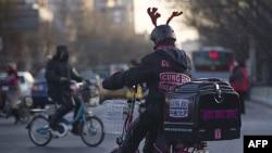 Một người dùng xe đạp chạy bằng điện đi giao bánh pizza ở Bắc Kinh