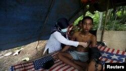Seorang dokter memeriksa kesehatan Deden, seorang remaja dengan ayah yang menderita kesehatan mental dan hidup dirantai ke pohon di pinggir sawah dekat rumah keluarga mereka di Desa Longkewang, Serang, Banten (23/3). (foto: REUTERS/Beawiharta)