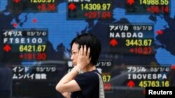 A woman walks past an electronic board displaying Japan's Nikkei average (top C) and various countries' stock price indices outside a brokerage in Tokyo, July 5, 2013.