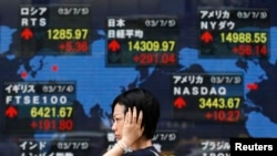 FILE - A woman walks past an electronic board displaying Japan's Nikkei average (top C) and various countries' stock price indices outside a brokerage in Tokyo.
