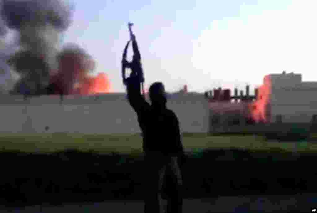 This image from video shows a building at the Syrian government checkpoint on fire in Dael, Syria, March 28, 2013.
