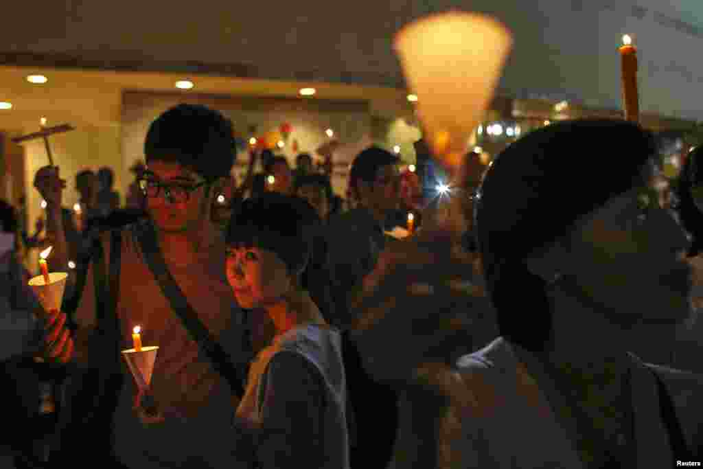People hold candles during an anti-violence campaign in center of Bangkok. Thailand's finance minister expressed concern about damage to the economy as government supporters and opponents prepare for big rallies this month that risk pushing the divided country to brink of chaos.