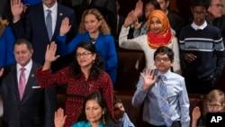 Rashida Tlaib (tengah, baju merah) dan Ilhan Omar (berjilbab) saat disumpah sebagai anggota Kongres AS di Gedung Capitol, 3 Januari 2019.