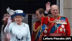 FILE - In this Saturday, June 14, 2014 file photo, Britain's Queen Elizabeth II, accompanied by Prince Philip, wave to the crowds from the balcony of Buckingham Palace, during the Trooping The Colour parade, in central London.