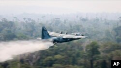 Na ovoj fotografiji koju je objavilo brazilsko ministarstvo odbrane, avion C-130 Hercules izbacuje vodu na prašumu u oblasti Amazona, u Brazilu, 24. avgusta 2019.