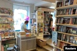 Seorang pelanggan melihat barang-barang di toko buku di kota kecil pantai timur Trosa, Swedia, 11 Agustus 2021. (REUTERS/Anna Ringstrom)