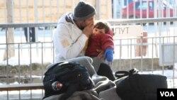Čovek i dete pokušavaju da se ugreju dok čekaju na registraciju u centru za izbeglice u Preševu, Srbija (P. Walter Wellman/VOA)