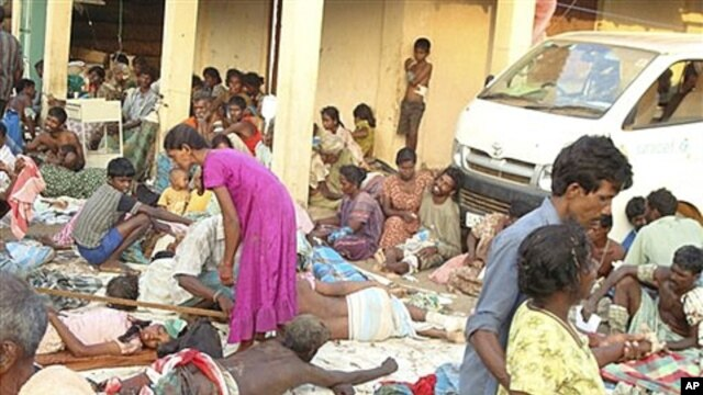 Sri Lankan ethnic Tamil victims of a shell attack wait outside a makeshift hospital in Tiger controlled No Fire Zone in Mullivaaykaal, May 10, 2009