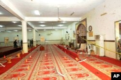 FILE - In this photo released by the Saudi Press Agency SPA, Saudi officials and investigators, background, check a mosque inside a police compound after a suicide bombing attack in of Abha, the provincial capital of Asir, Saudi Arabia, Aug. 6, 2015.