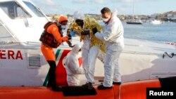 Un sobreviviente africano es ayudado a bajar de un bote en Lampedusa.