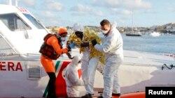 Petugas penjaga pantai Italia menolong seorang migran yang selamat mendarat di Pulau Lampedusa (11/2).