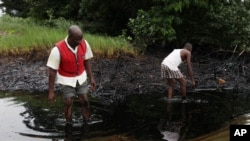 FILE - In this Sunday June 20, 2010 file photo, men walk in an oil slick covering a creek near Bodo City in the oil-rich Niger Delta region of Nigeria. (AP Photo/Sunday Alamba, FILE)
