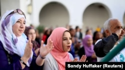 Yesmeena Buzeriba (tengah) bernyanyi bersama mahasiswa lain dalam aksi menentang Islamofobia di San Diego State University di San Diego, California, 23 November 2015. (Foto: REUTERS/Sandy Huffaker)