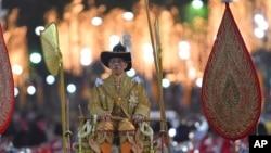 Thailand's King Maha Vajiralongkorn is transported on the royal palanquin by royal bearers during the Royal Procession outside the Grand Palace in Bangkok, Thailand, Thursday, Dec. 12, 2019. (AP Photo/Suganya Samnangjam)