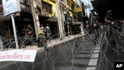 Thai soldiers and riot policemen stand beside barbed wire after they sealed off part of a tourist district on Sukhumvit road in downtown Bangkok, on Monday.