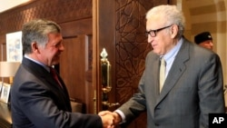 In this photo released by the Jordanian Royal Palace, Jordan's King Abdullah II, left, shakes hands with U.N. envoy on Syria, Lakhdar Brahimi, at the Royal Palace in Amman, Jordan, Oct. 23, 2013.