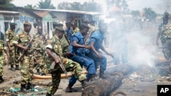 Policiers et soldats dégagent la rue barrée par des barricades, Bujumbura, 25 mai 2015.