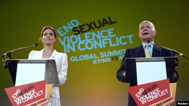 Actress and special envoy of the UN High Commissioner for Refugees (UNHCR), Angelina Jolie, and British Foreign Secretary William Hague make their opening speeches at a global summit to end sexual violence in conflict in London, June 10, 2014.