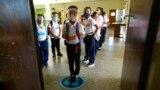 Los estudiantes esperan instrucciones para ingresar a su salón de clases el primer día de regreso a la escuela presencial desde el inicio de las restricciones por el COVID-19, en una escuela pública en Caracas,. Octubre 25, 2021.