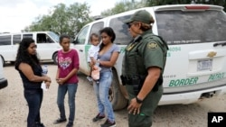 U.S. Border Patrol agent-in-charge Melissa Lucio, right, talks with women and children migrating from Honduras after they surrendered to U.S. Border Patrol agents after illegally crossing the border Monday, June 25, 2018, near McAllen, Texas. (AP Photo/Da