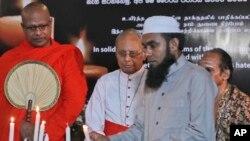 Ulama Islam Sri Lanka, menyalakan lilin dan didampingi seorang bhiksu Budha, kiri, pendeta Hindu, kanan, dan uskup Kristen, dalam sebuah acara solidaritas dengan seluruh korban dari serangan Hari Paskah, Minggu, di Kolombo, Sri Lanka, Minggu, 28 April 2019 (foto: AP Photo/Manish