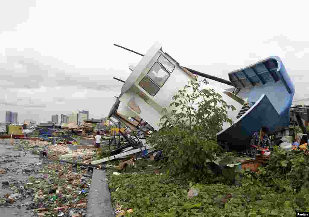 People walk near a boat destroyed by Typhoon Rammasun which battered the coastal bay of Baseco compound, metro Manila, July 16, 2014.