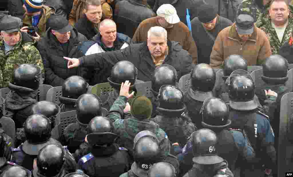 Một người biểu tình đôi co với cảnh sát trước Quốc hội Ukraine ở Kiev. Các nhà lập pháp Ukraine bỏ phiếu với tỉ lệ áp đảo bãi bỏ vị thế không liên kết của Ukraine, mở đường cho việc xin gia nhập khối NATO.