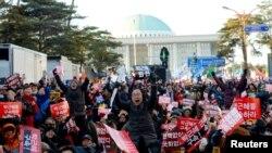 "Warga bereaksi di depan Majelis Nasional di Seoul, Korea Selatan, usai disahkannya hasil pengambilan suara pemakzulan Presiden Korea Selatan Park Geun-hye, dengan membawa spanduk bertuliskan ""Dakwa Park Geun-hye"", 9 Desember 2016 (Foto: News1 via REUTERS)."
