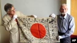 """2017年8月7日,93岁的美国二战老兵马文·斯特罗姆伯(右)与""""盂兰盆协会""""执行主任雷克斯·兹卡展示斯特罗姆伯70多年前从一名战死日军身上取下的""""武运长久""""旗。斯特罗姆伯将亲自把这面旗还给死者的家人。"""